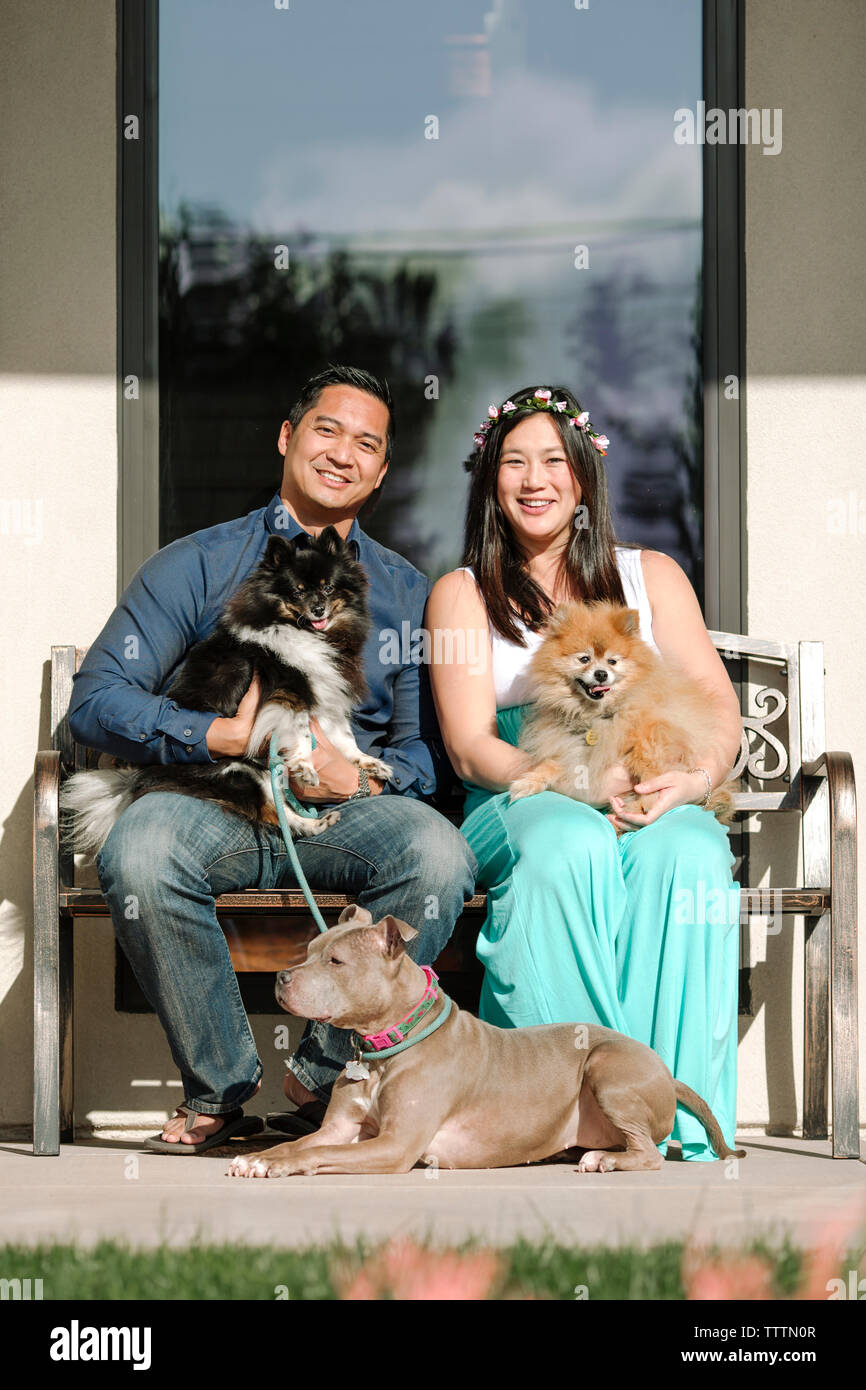 Portrait of confident smiling couple with dogs sitting on bench against house - Stock Image