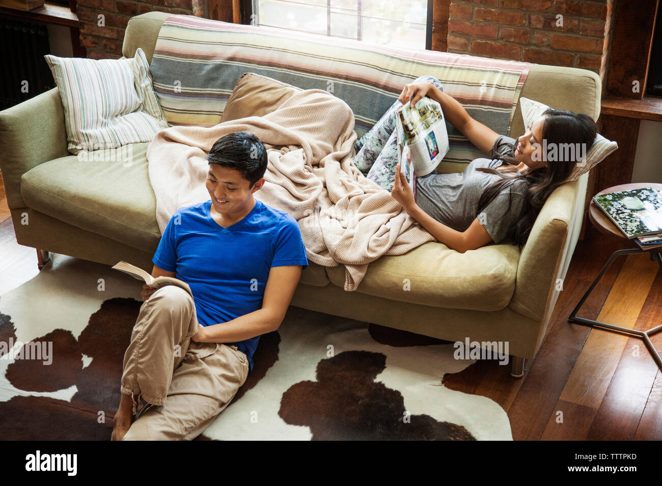 Couple reading book and magazine while relaxing at home - Stock Image