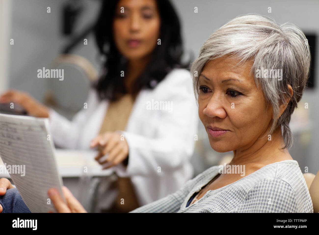 Doctor reading medical report Stock Photo