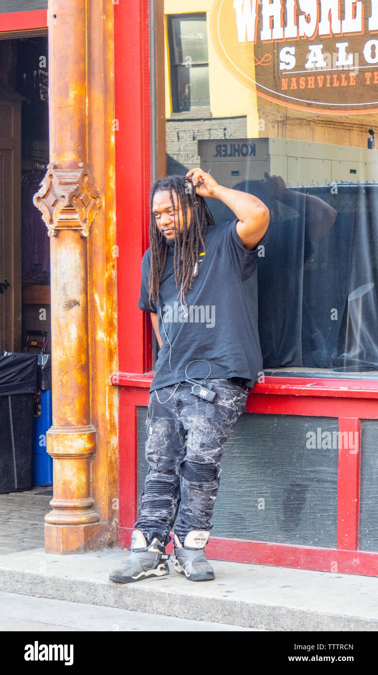 Afro-American male with dreadlock hair scratching his head standing on Broadway Nashville Tennessee USA. - Stock Image