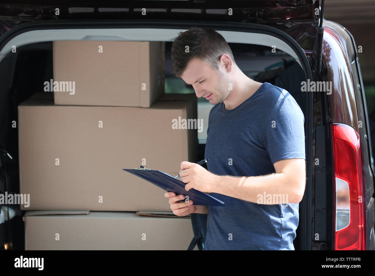Young male deliverer noting executing of order - Stock Image