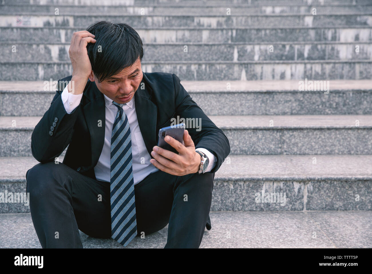 Asian businessmen with headaches or migraines at the city hall after work Images of young businessmen who are tired, stress, crisis, depression, failu - Stock Image