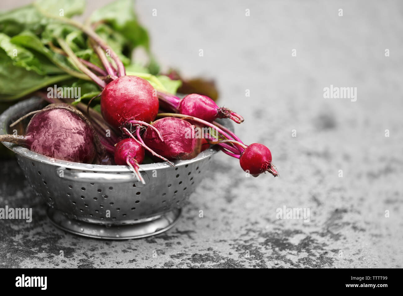 Bunch of fresh beets in a colander on grey background Stock Photo