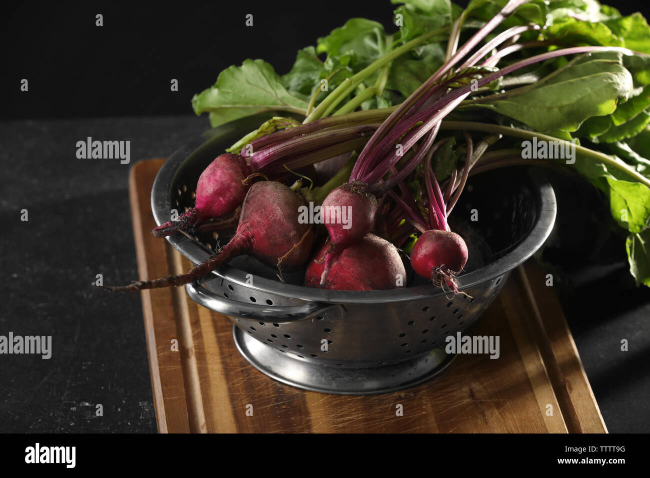 Bunch of fresh beets in a colander on wooden board Stock Photo