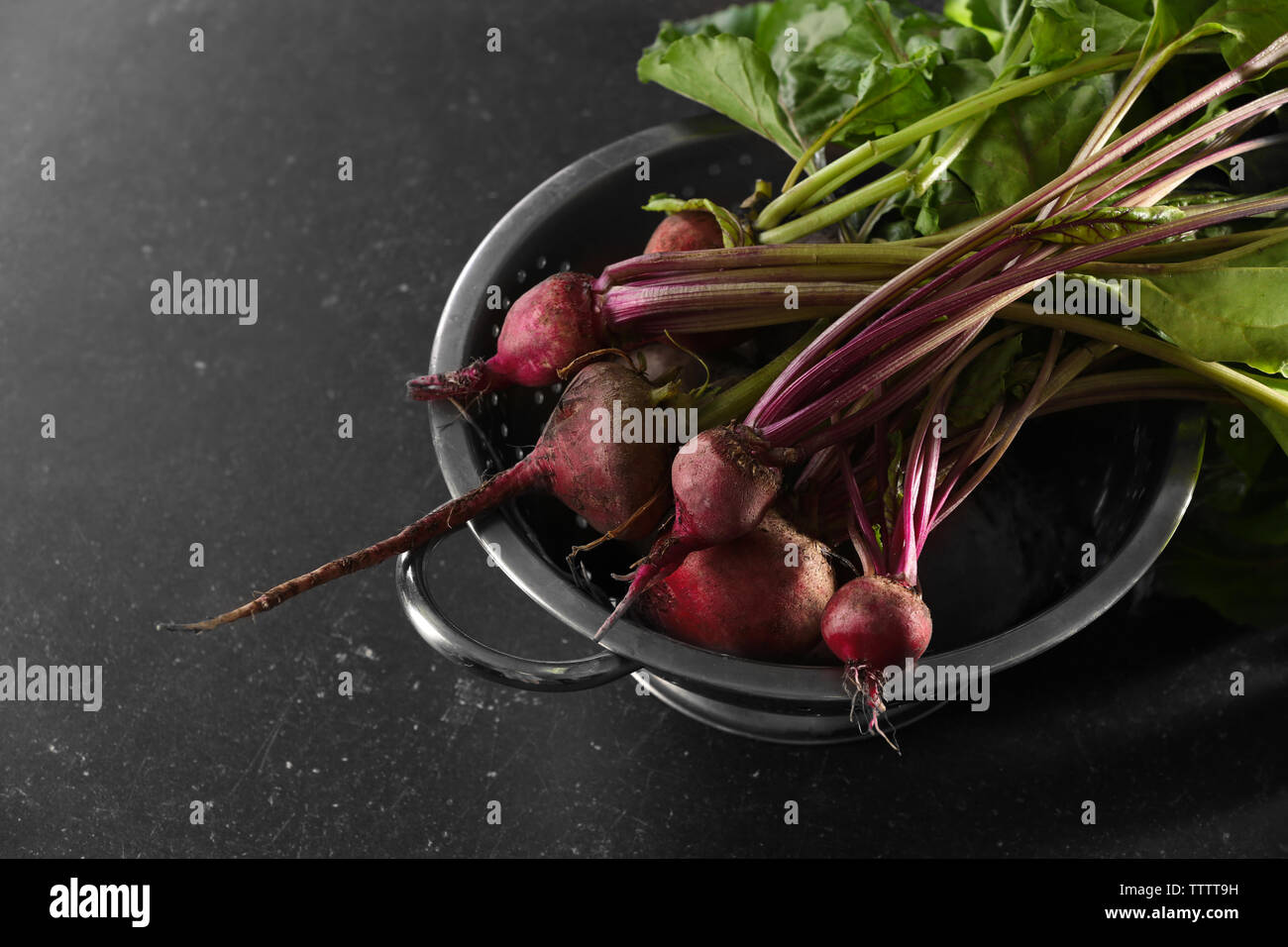 Bunch of fresh beets in a colander on black background Stock Photo