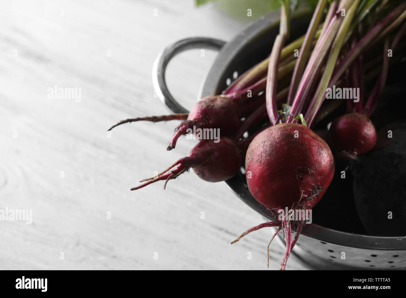 Bunch of fresh beets in a colander on light wooden background Stock Photo