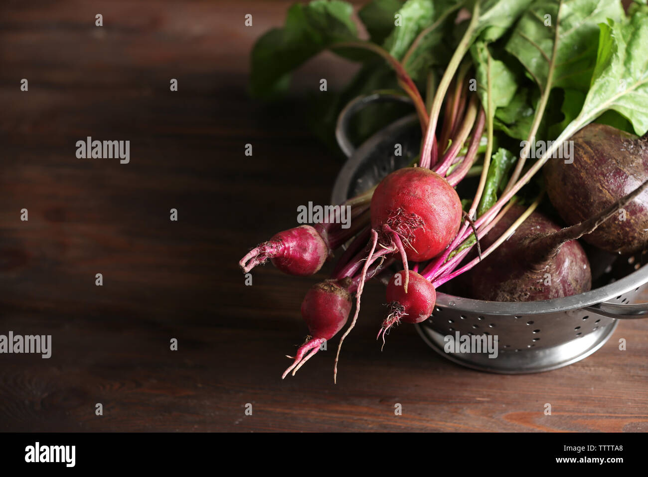 Bunch of fresh beets in a colander on wooden table Stock Photo