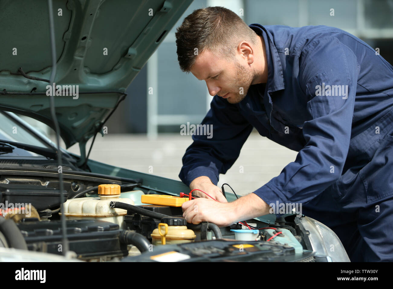 Mechanic with scan tool diagnosing car in open hood. Closeup - Stock Image
