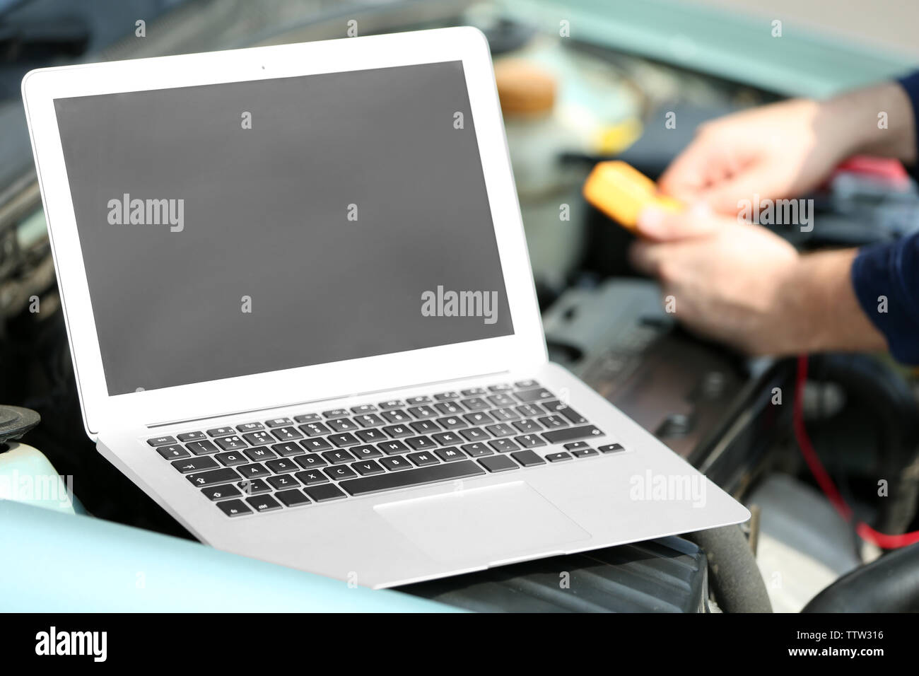 Computer diagnosing of car. Laptop in open hood - Stock Image