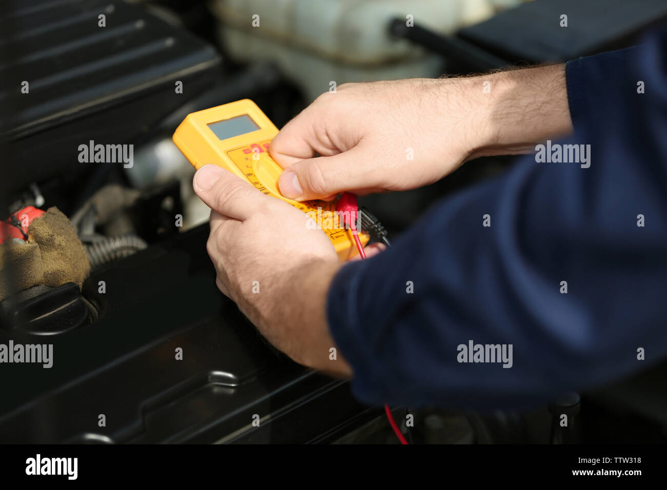 Hands of mechanic with a device for the diagnosing car - Stock Image