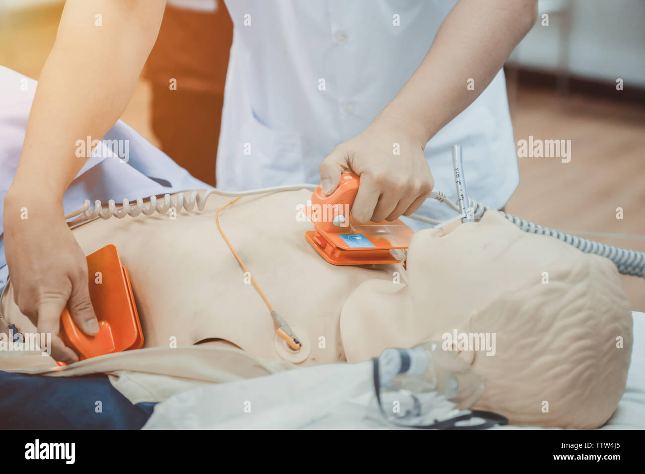 hands of doctor holding defibrillator electrods, performing defibrillation or electropulse therap Stock Photo