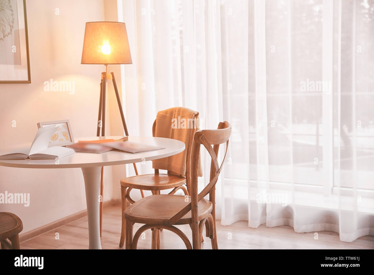 Table with chairs in light room interior - Stock Image