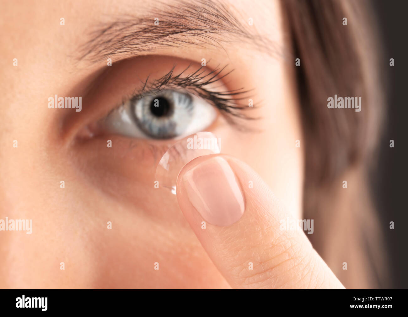 Close up view of young woman putting contact lens in her eye Stock Photo