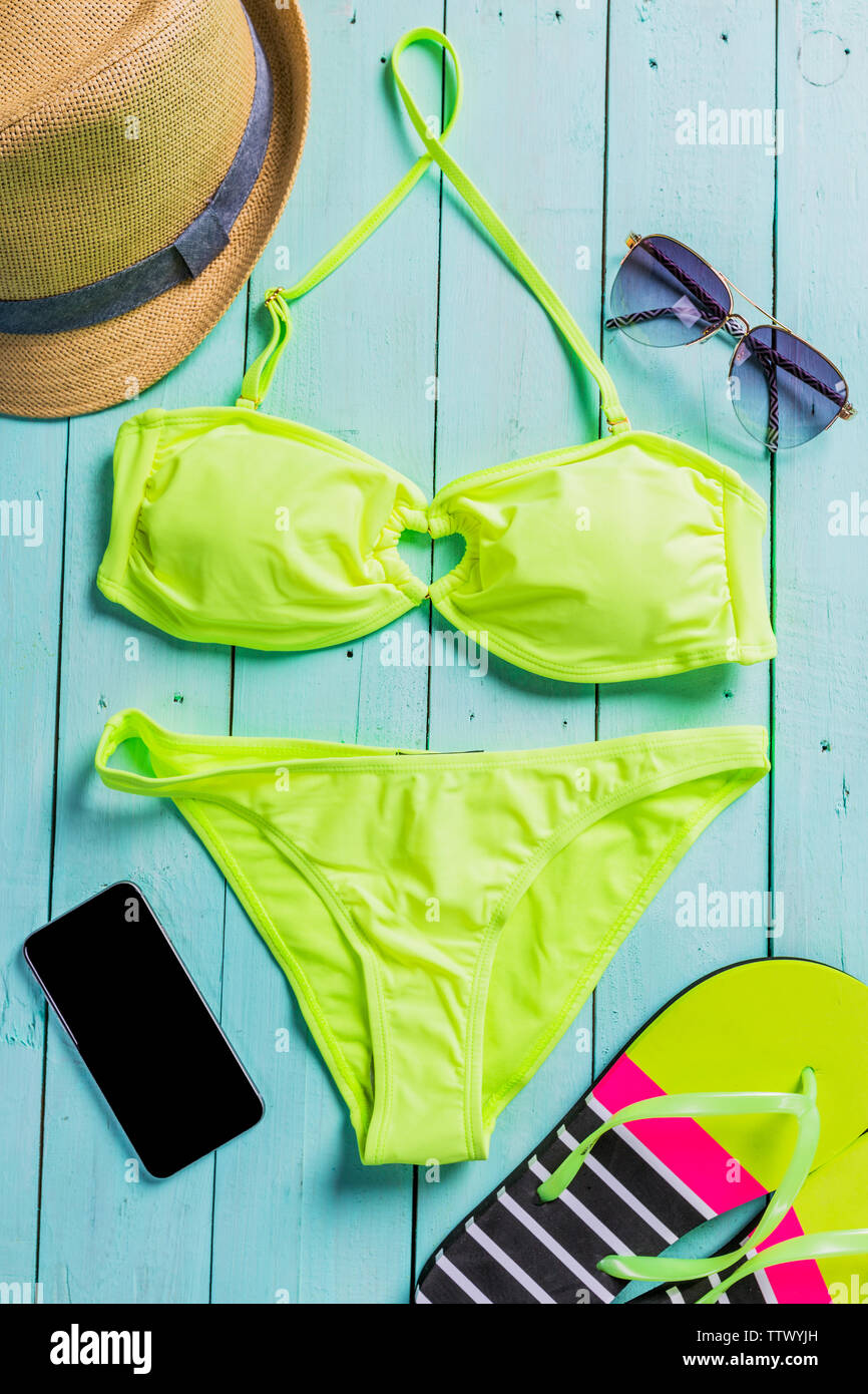 Beach accessories with yellow swimming suit,sunglasses and flip flops - Stock Image