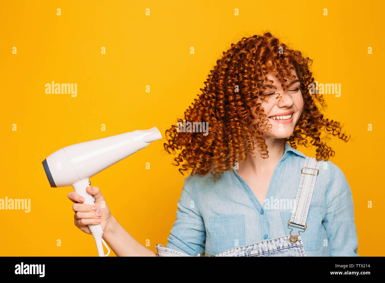 curly red-haired woman using hair dryer on yellow background. Making perfect curls Stock Photo