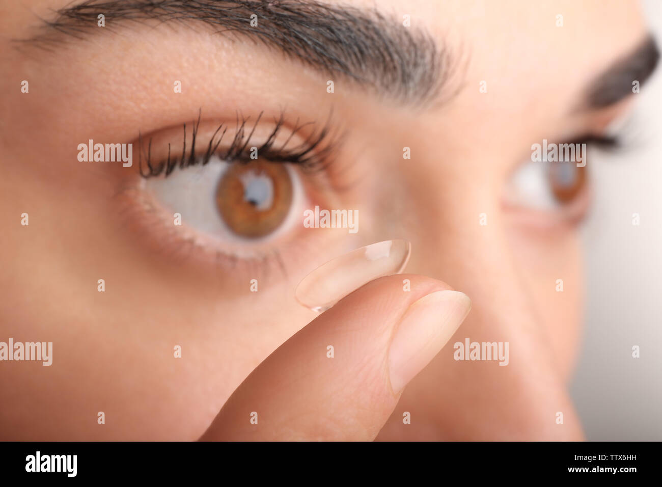 Young woman putting contact lens in her eye, close up view. Medicine and vision concept Stock Photo