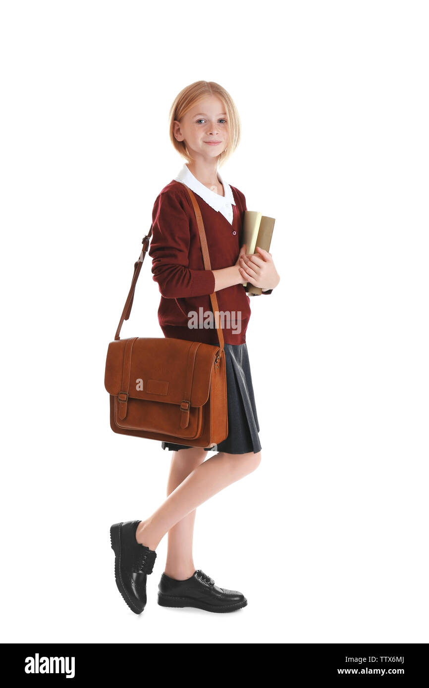 Schoolgirl with books and bag isolated on white - Stock Image