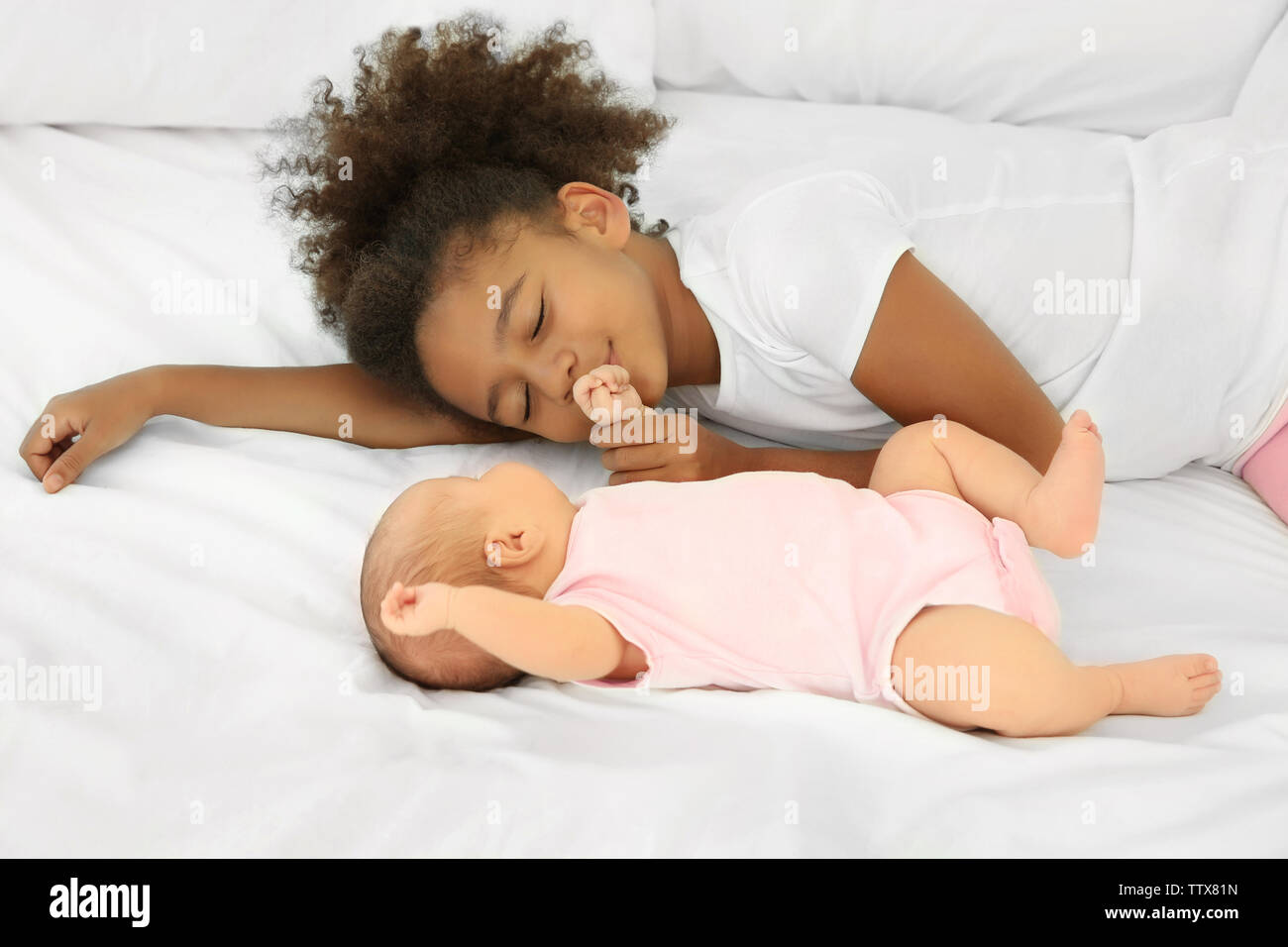 Cute baby and elder sister on bed - Stock Image