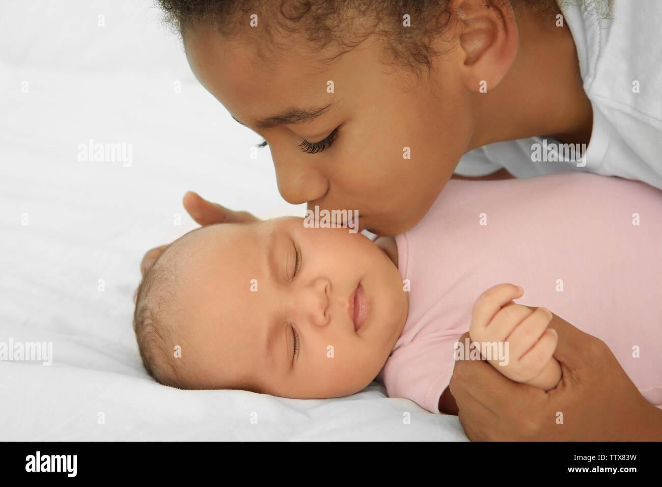 Girl kissing her little sister, closeup - Stock Image