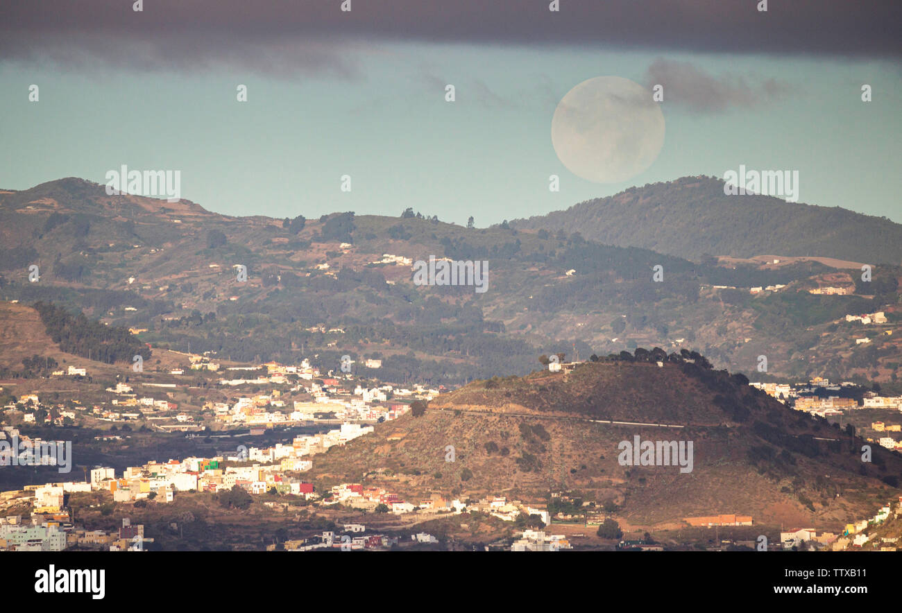 Las Palmas, Gran Canaria, Canary Islands, Spain. 18th June 2019. The Moon sets over the mountains of Gran Canaria on a glorious Tuesday morning in The Canary Islands. - Stock Image