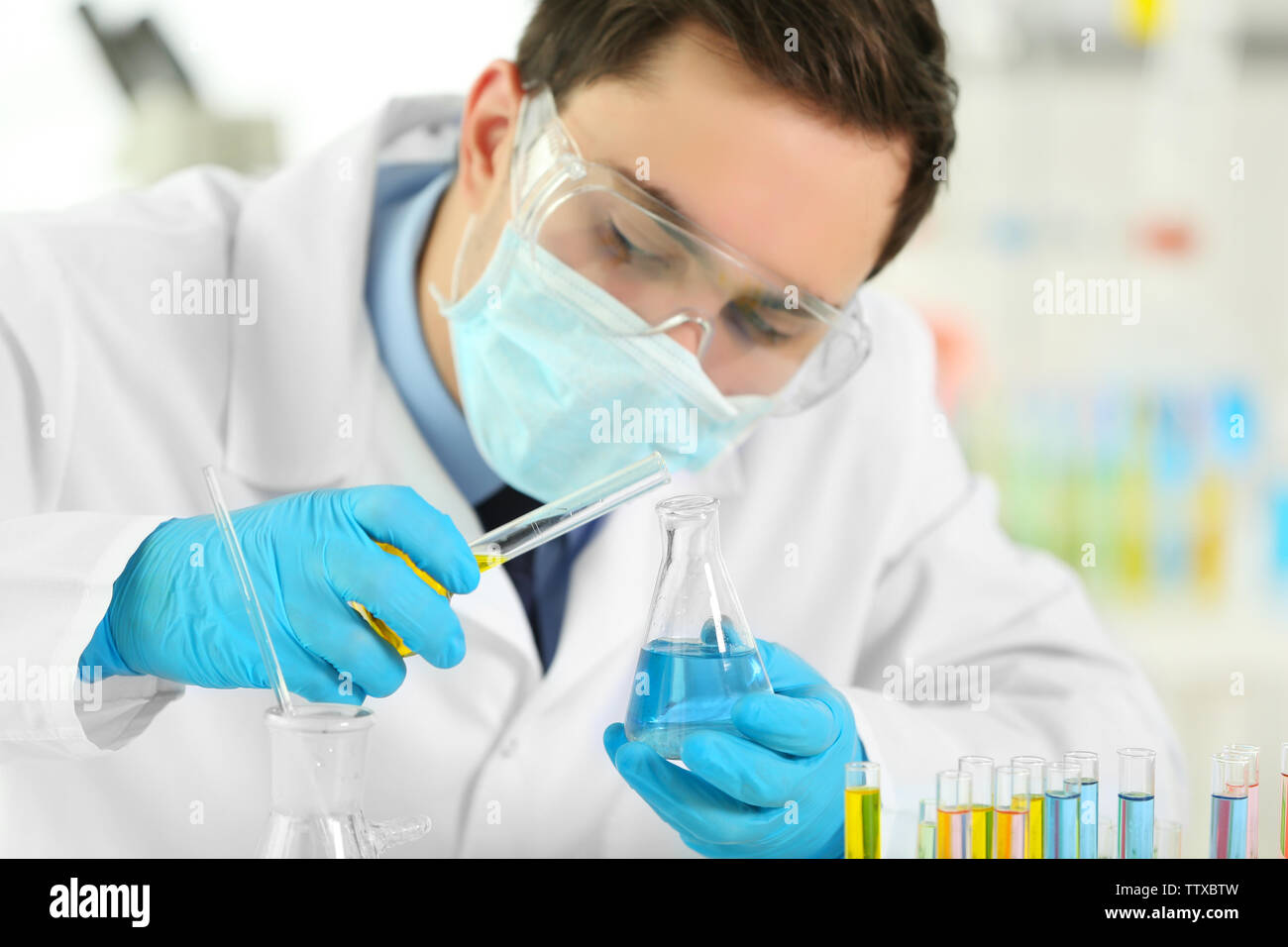 Young male scientist making experiments in laboratory - Stock Image