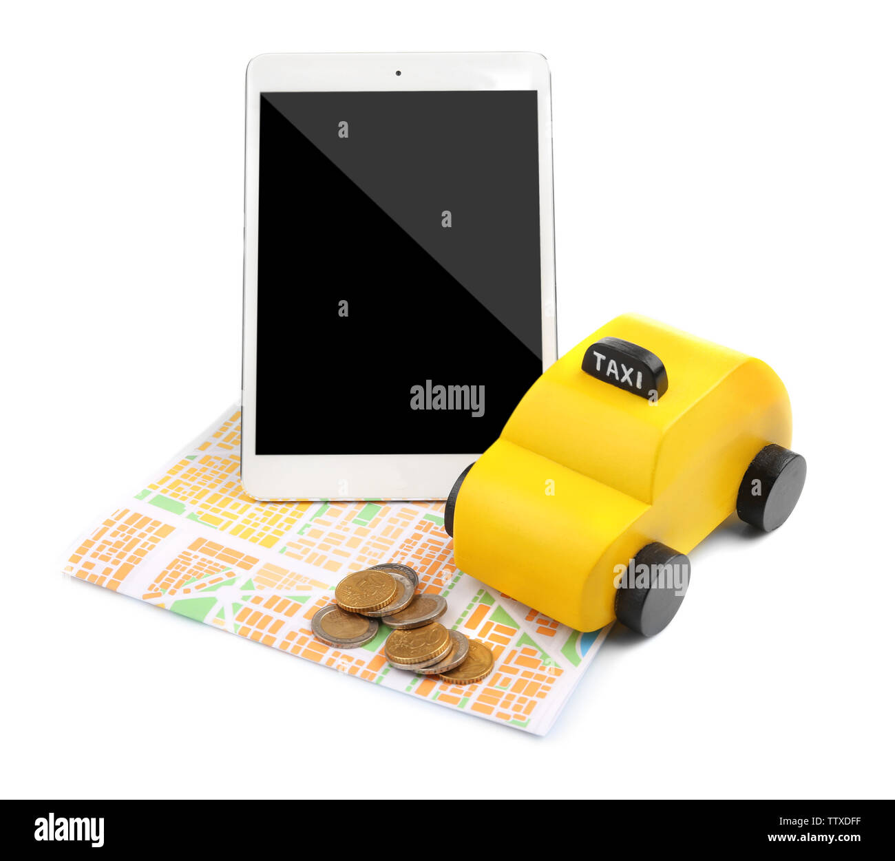 Yellow toy taxi, tablet, map and coins isolated on white - Stock Image