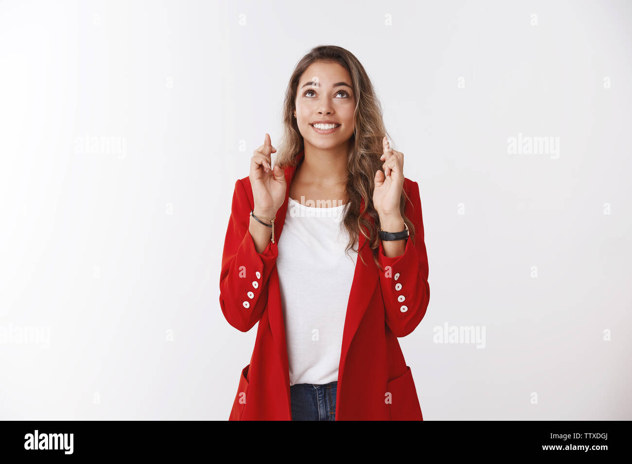 Upbeat excited charming optimistic cute female wearing red jacket praying looking skies cross fingers good luck anticiapting good news smiling broadly - Stock Image