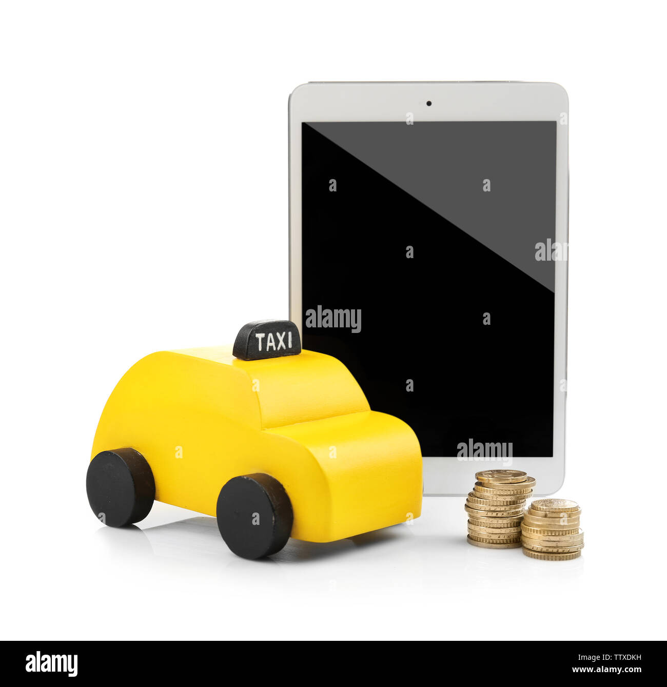 Yellow toy taxi cab, tablet and coins isolated on white - Stock Image