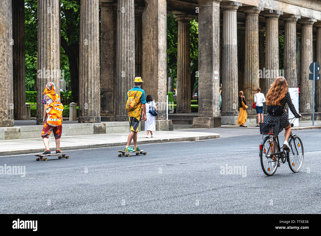 Young tourists in colourful clothing enjoying Summer, Museum Island, Mitte,Berlin. Two skate boarders & female cyclist - Stock Image
