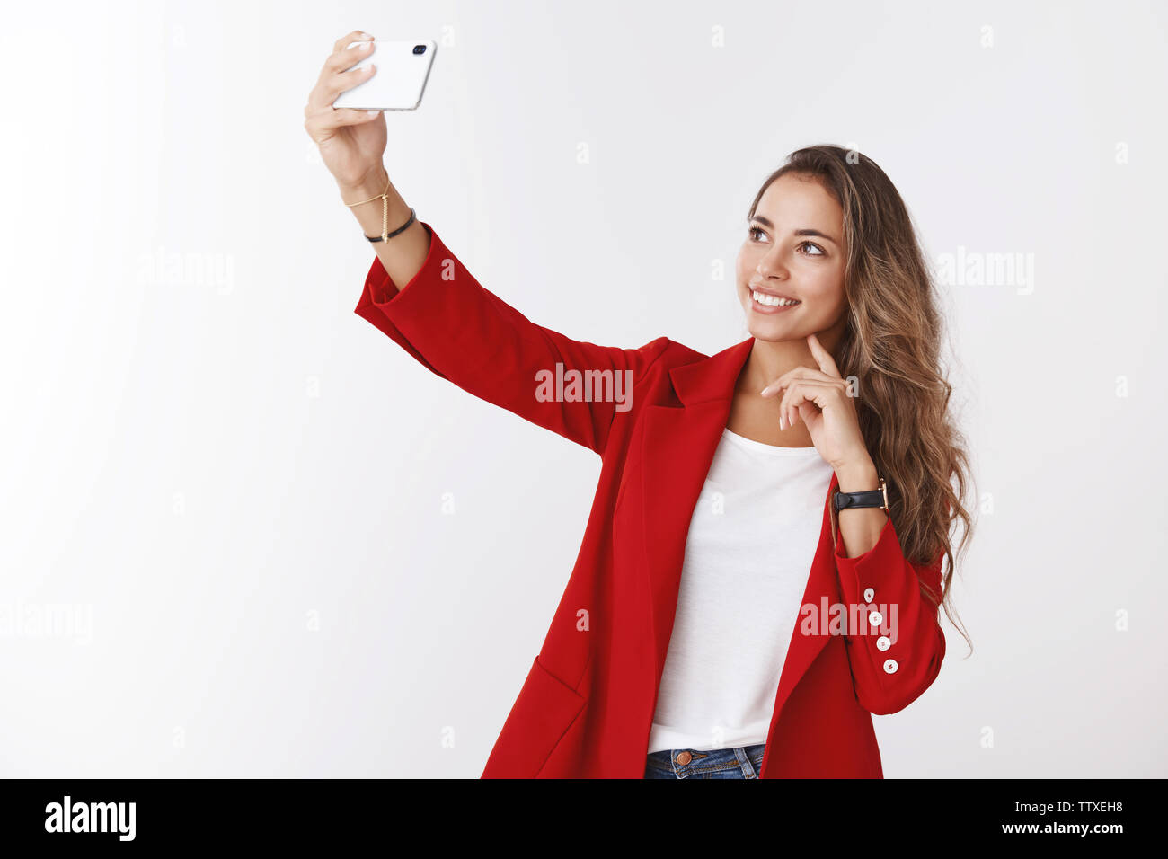 Charming modern female office employee taking selfie posting online blog telling followers new job, extending hand holding smartphone photographing - Stock Image