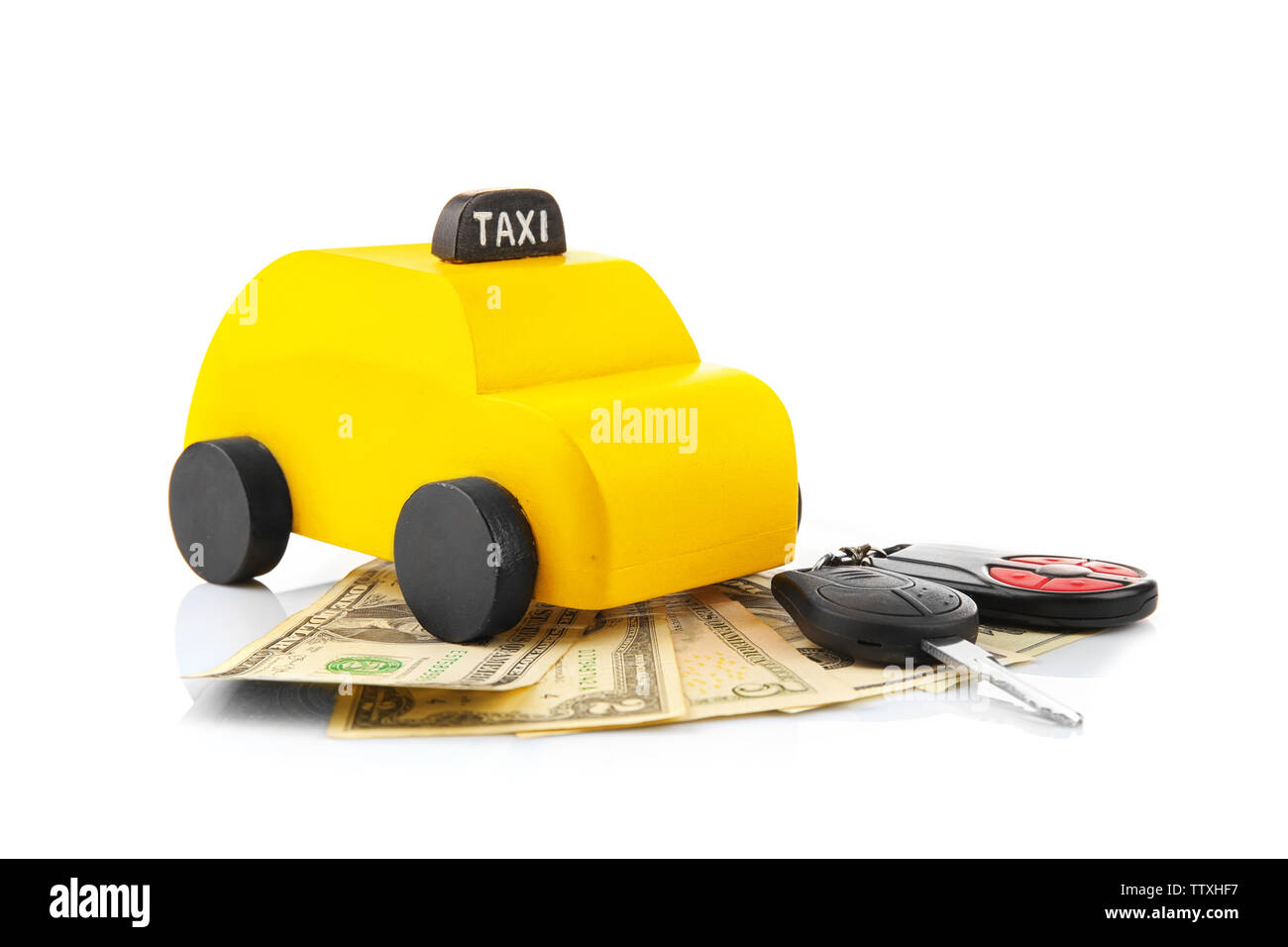 Yellow toy taxi with money and car key on white background - Stock Image