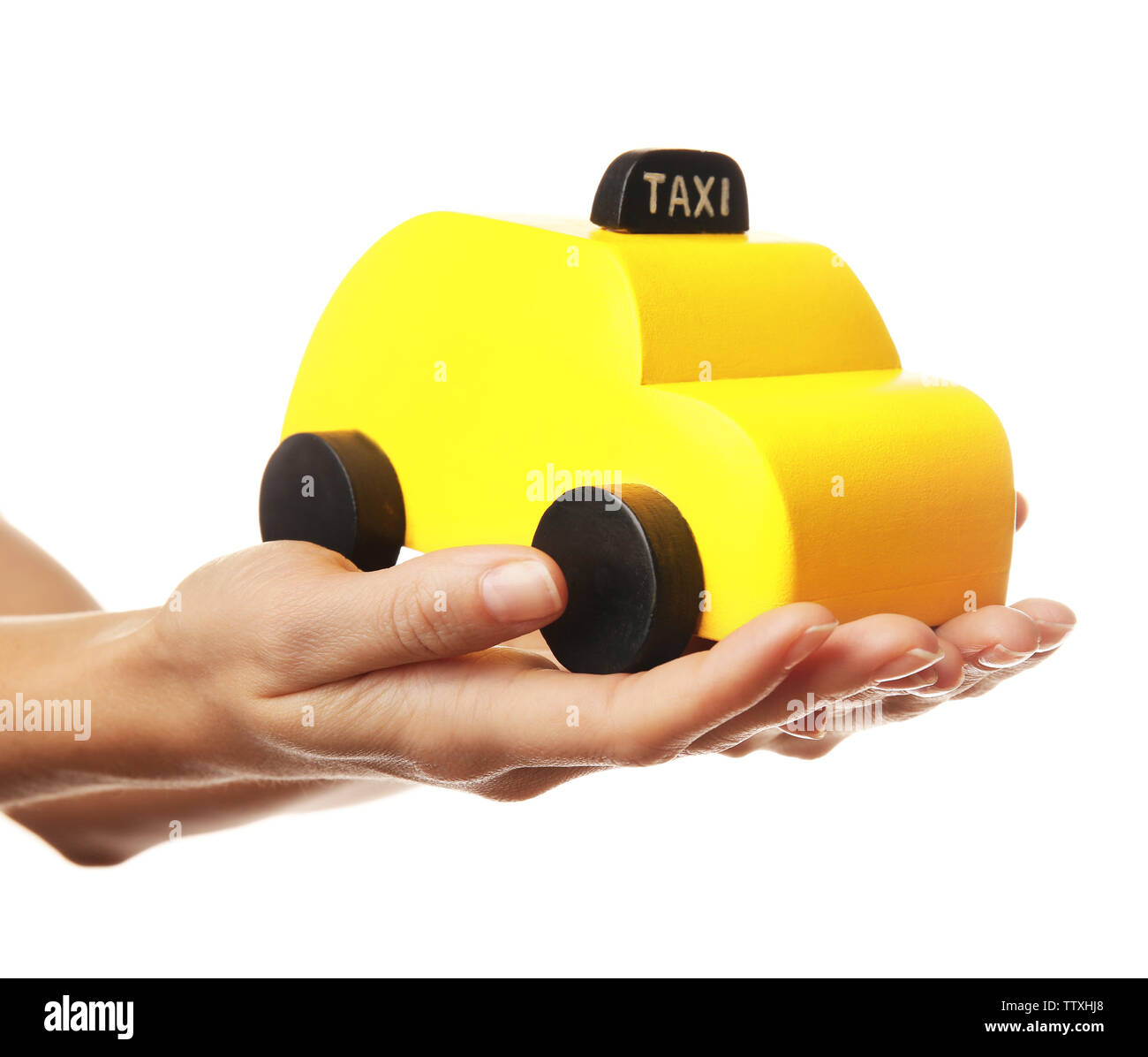 Woman holding yellow toy taxi on white background - Stock Image