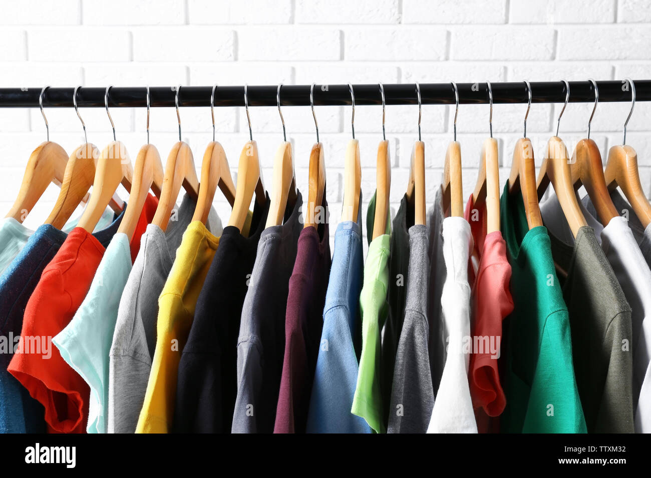 Colorful t-shirts on hangers against brick wall, close up