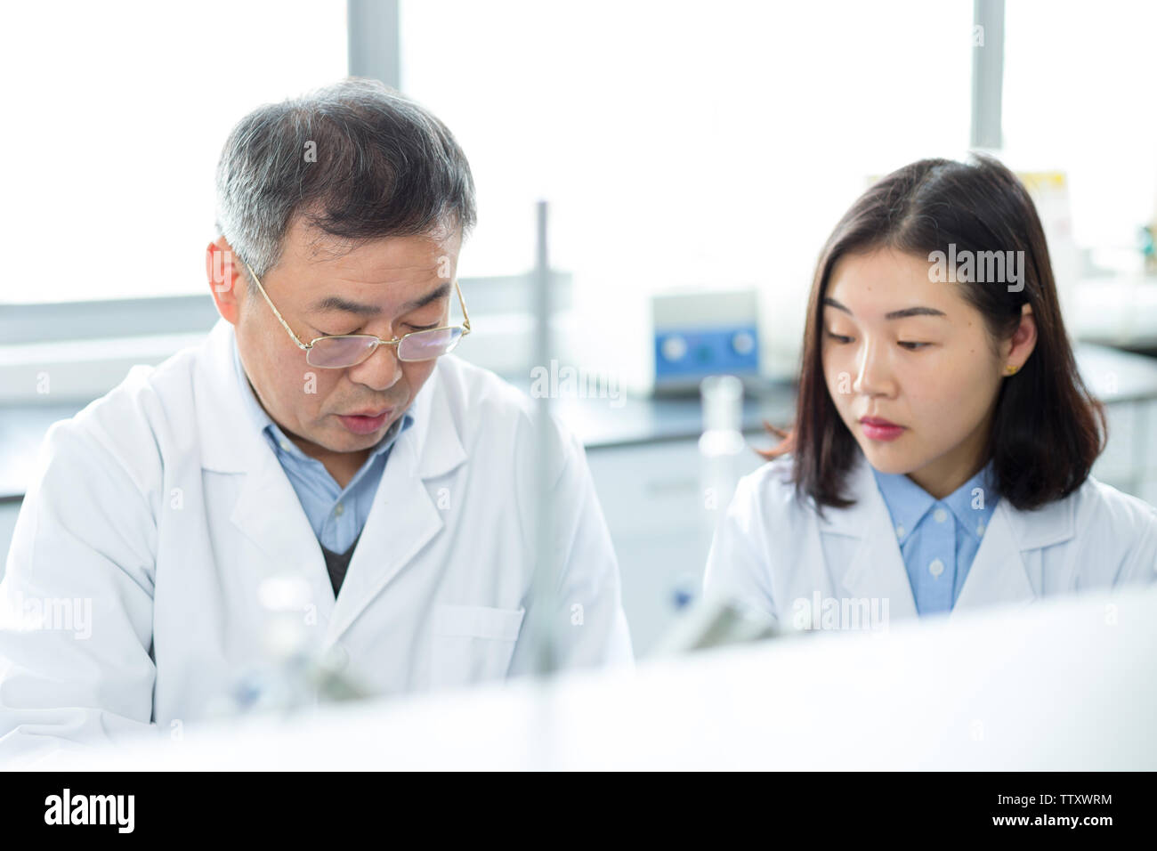 people doing chemical experiment in modern lab - Stock Image
