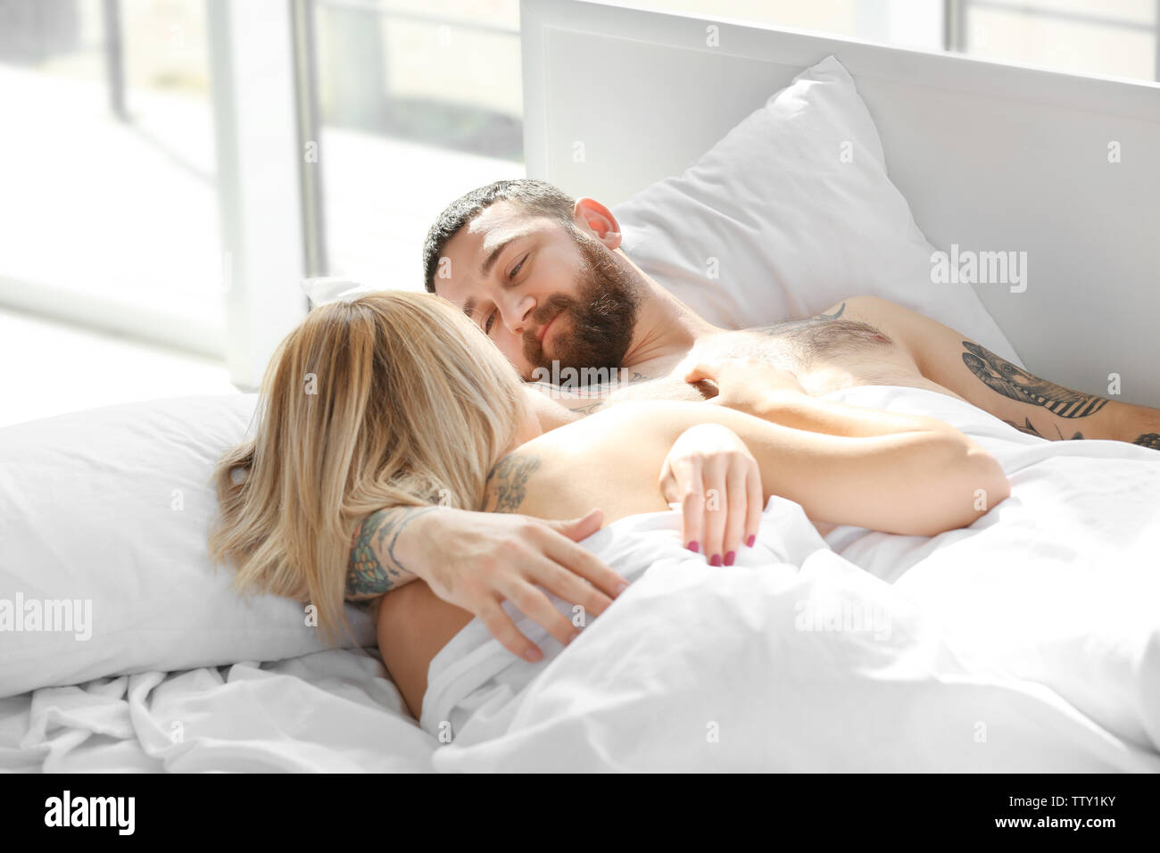 Tattooed couple sleeping in bed - Stock Image