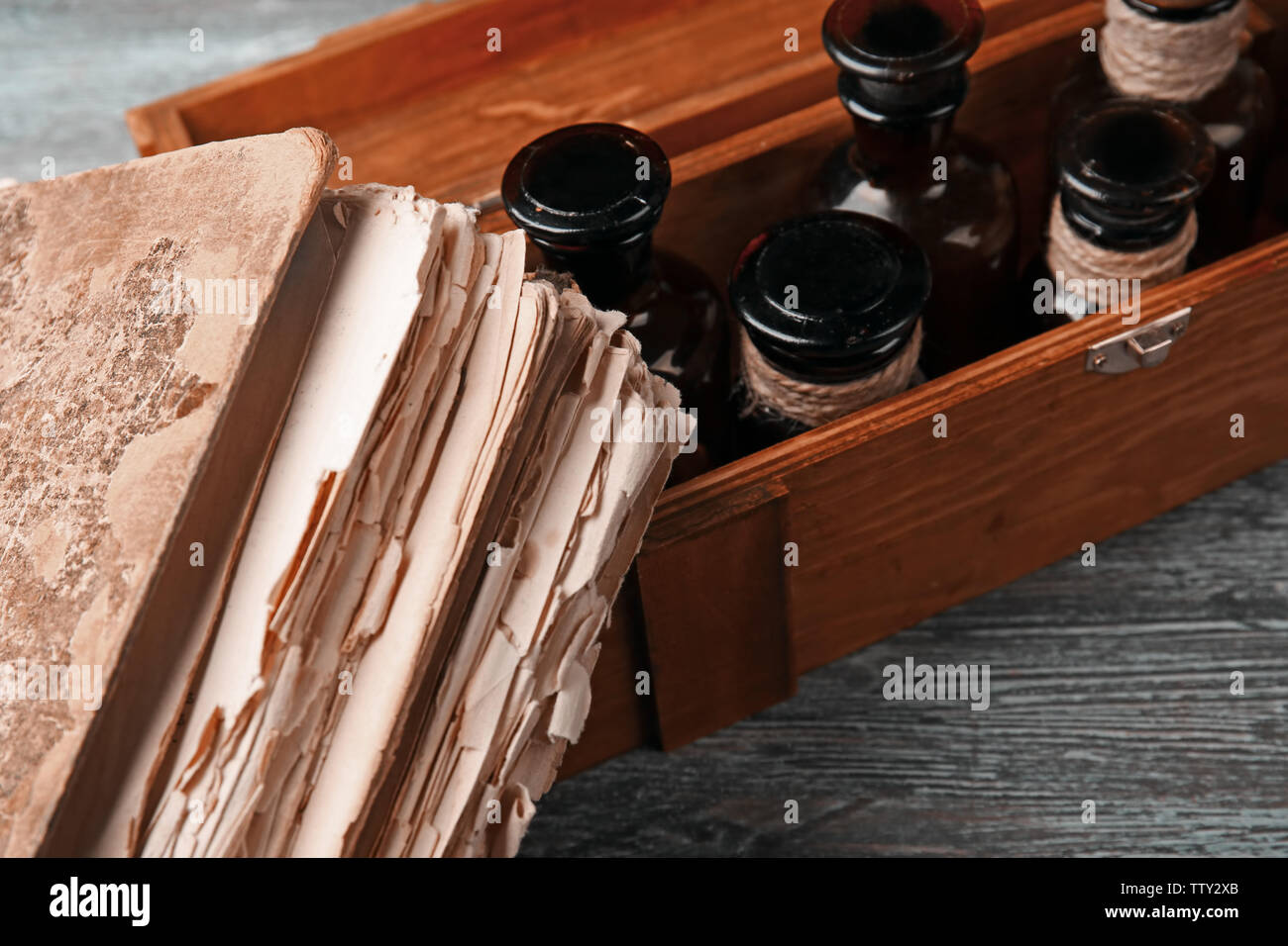 Vintage glass bottles in wooden box with old book, closeup - Stock Image