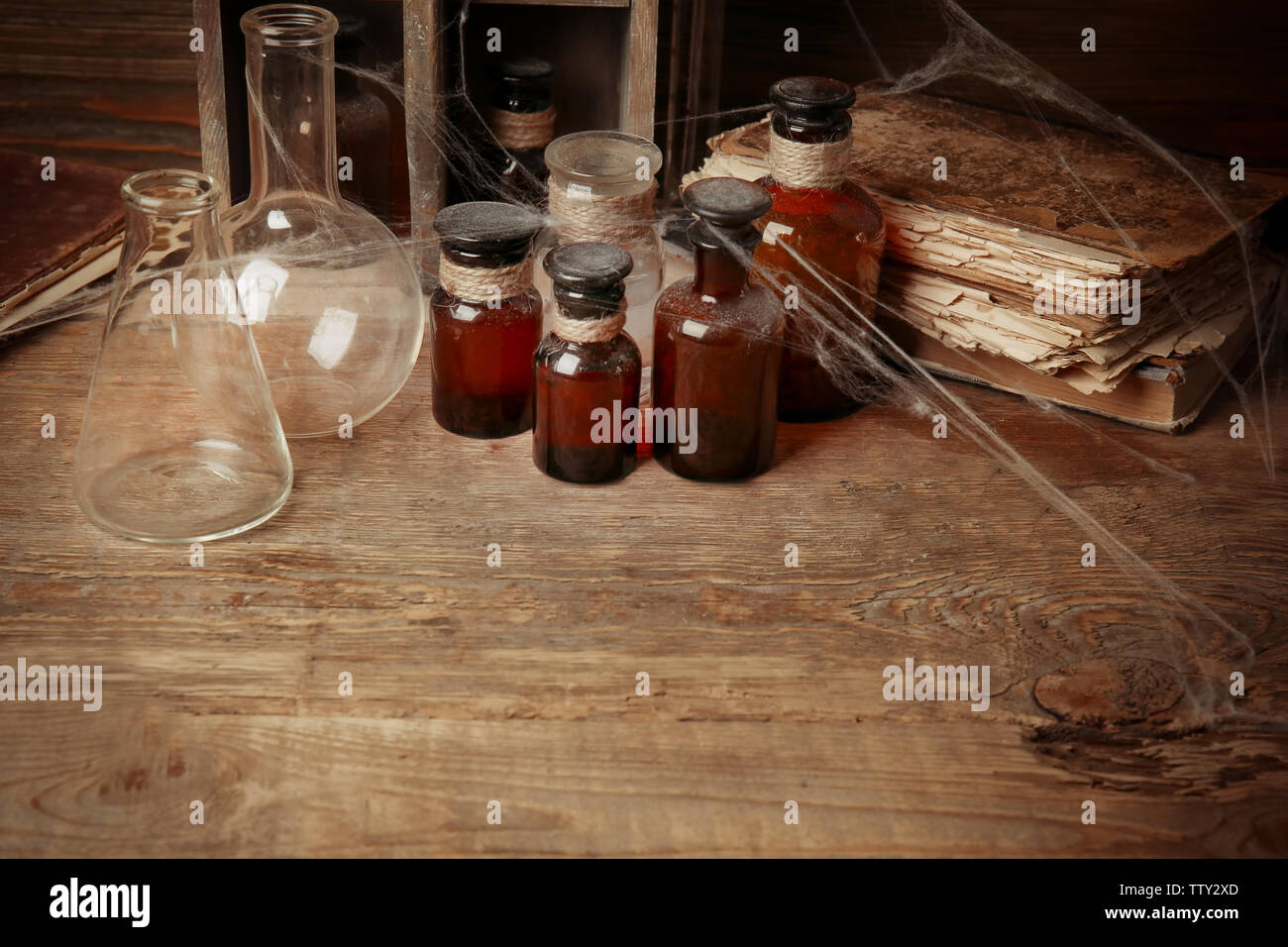 Vintage flasks and glass bottles with spiderweb on wooden background, closeup - Stock Image