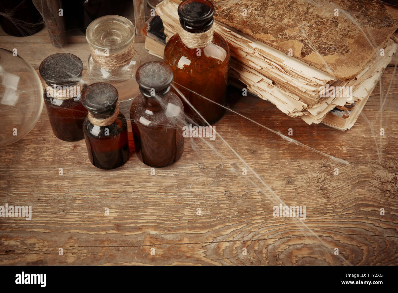 Vintage glass bottles and old books with spiderweb on wooden background, closeup - Stock Image