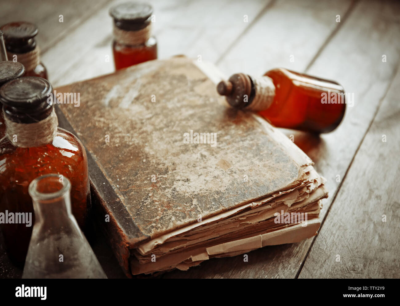 Old book with glass bottles on wooden background, closeup - Stock Image
