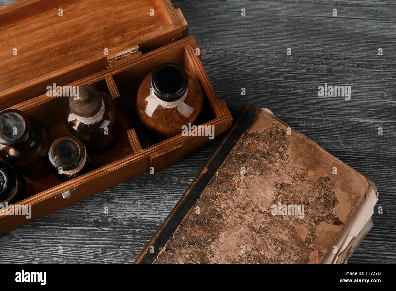 Vintage glass bottles in box with old book on wooden background, closeup - Stock Image