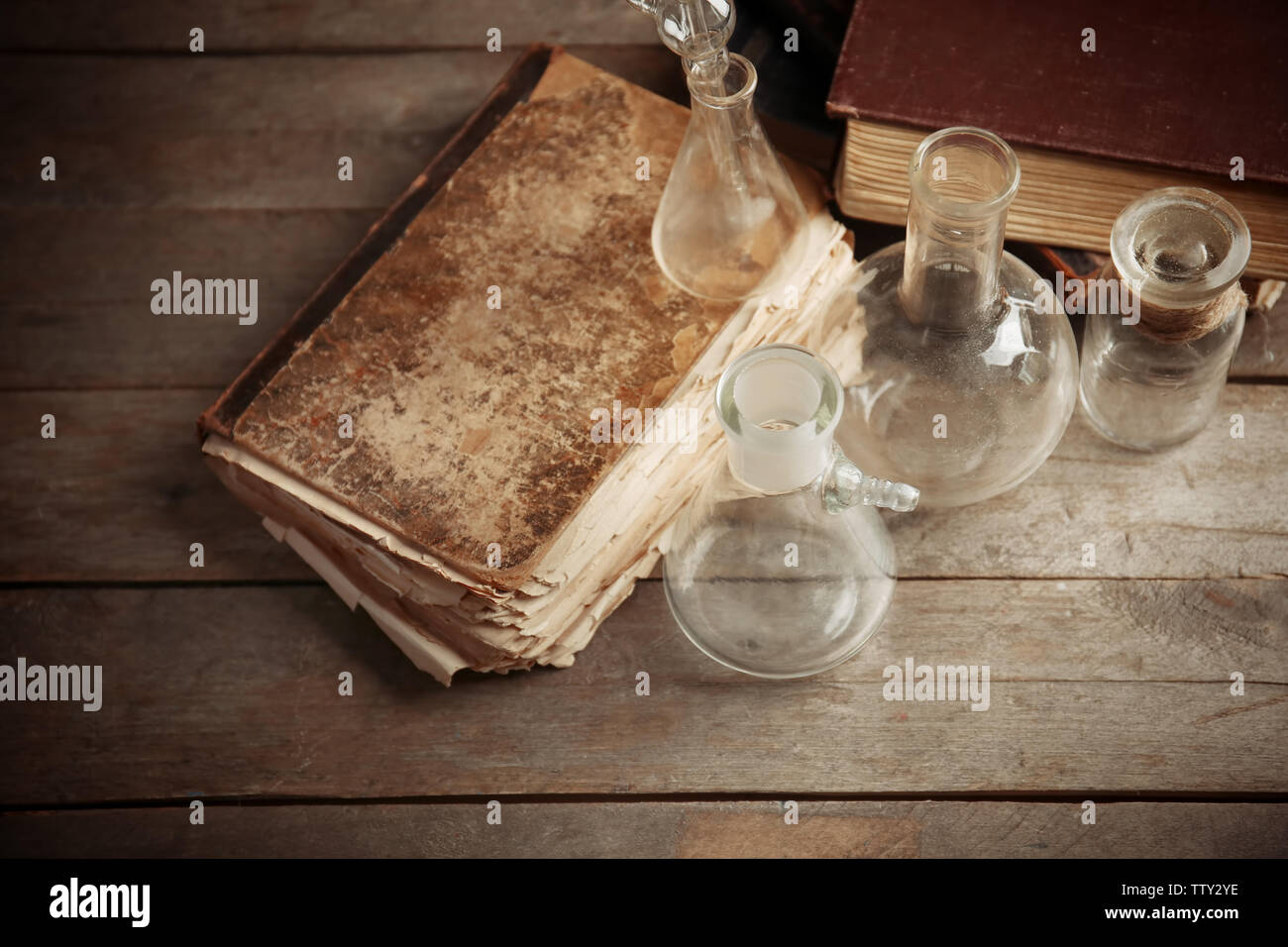 Glass flasks and old books on wooden background, closeup - Stock Image