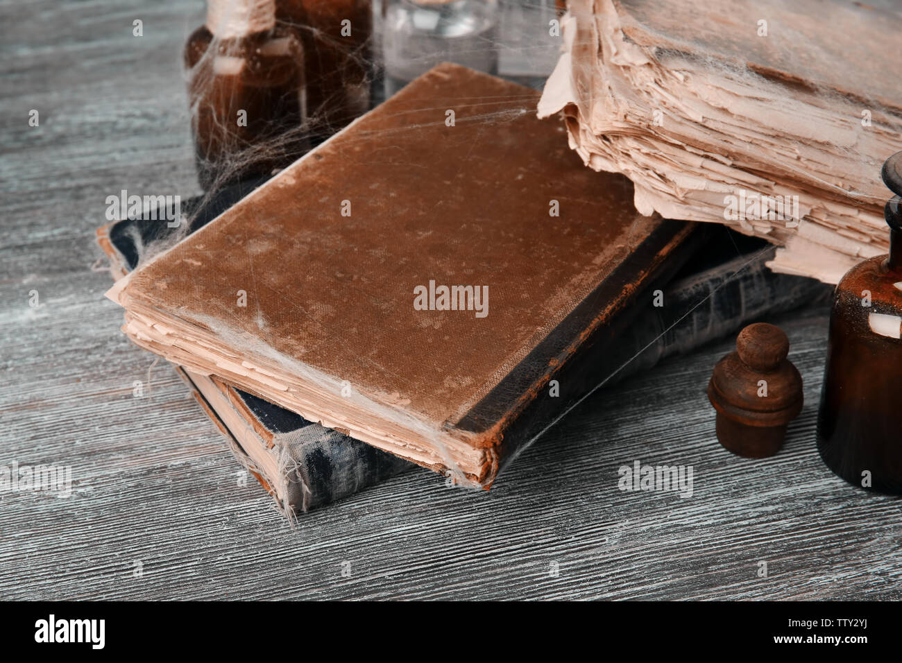 Old books with spiderweb on wooden background, closeup - Stock Image