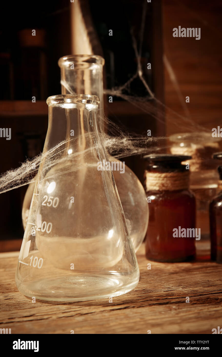Vintage glass flask with spiderweb, closeup - Stock Image