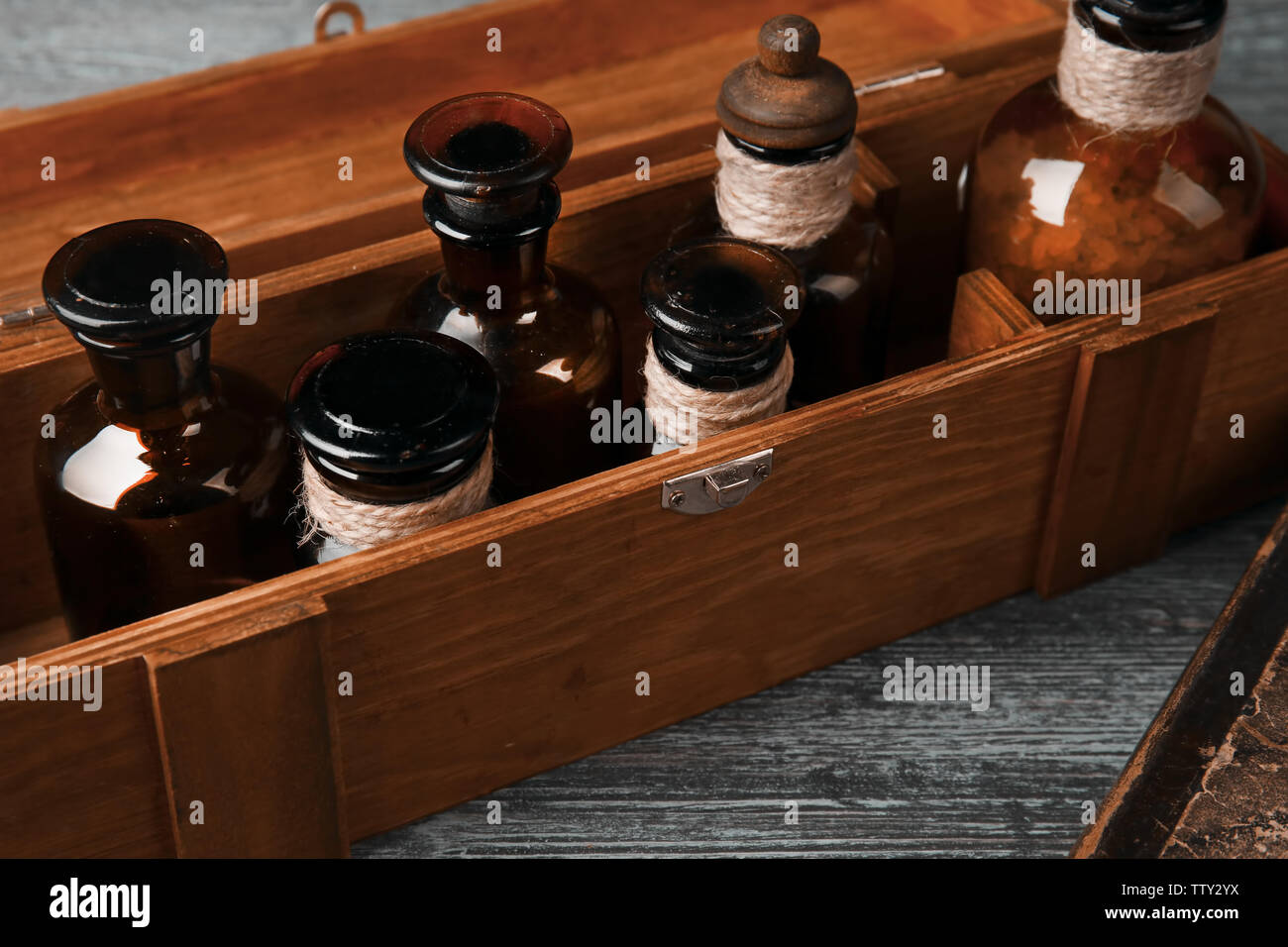 Vintage glass bottles in wooden box, closeup - Stock Image