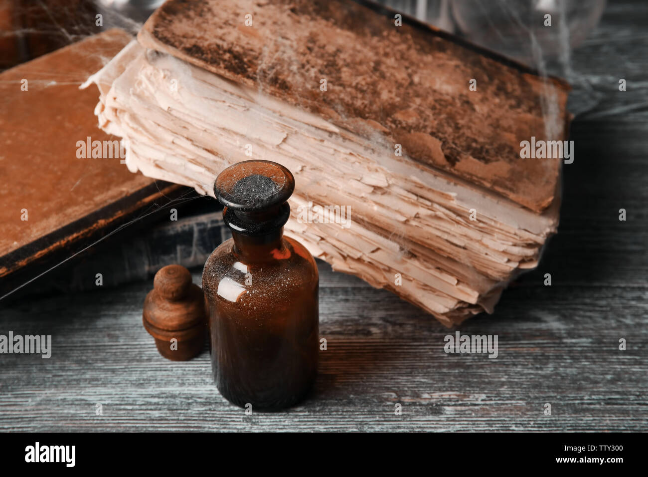 Vintage glass bottle with old books on wooden background, closeup - Stock Image