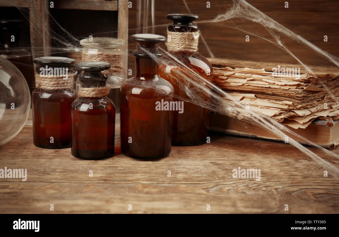 Vintage glass bottles and old books with spiderweb on wooden table, closeup - Stock Image