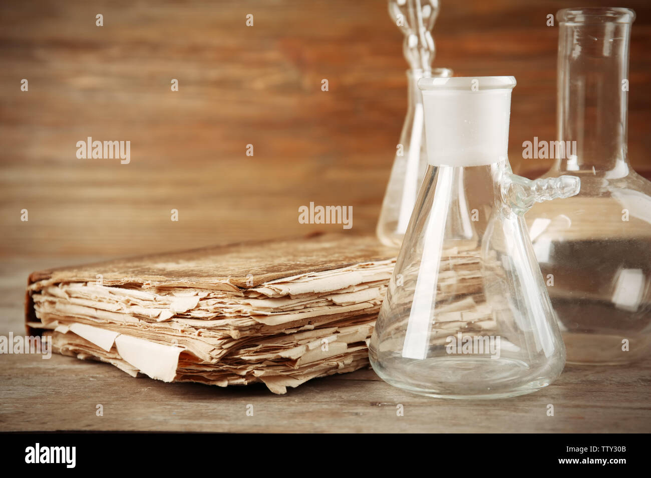 Glass flasks and old book on wooden table, closeup - Stock Image