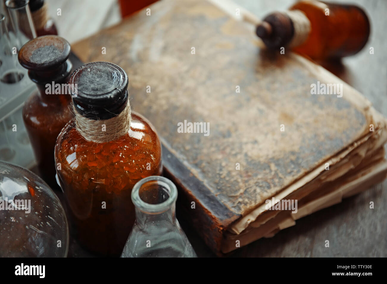 Old book with glass bottles, closeup - Stock Image