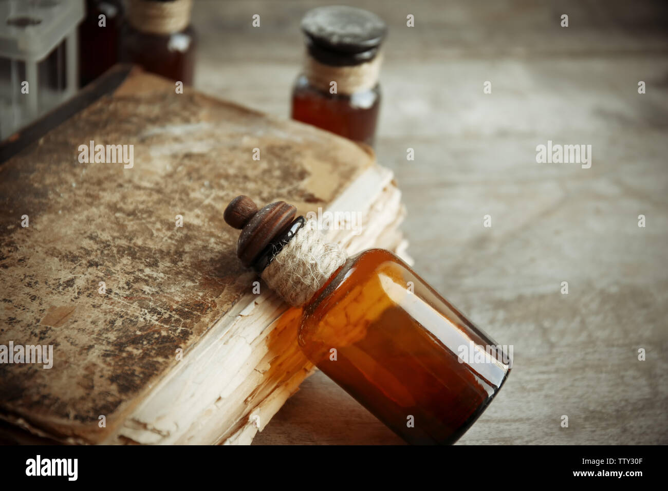 Vintage glass bottle with old book on wooden background, closeup - Stock Image