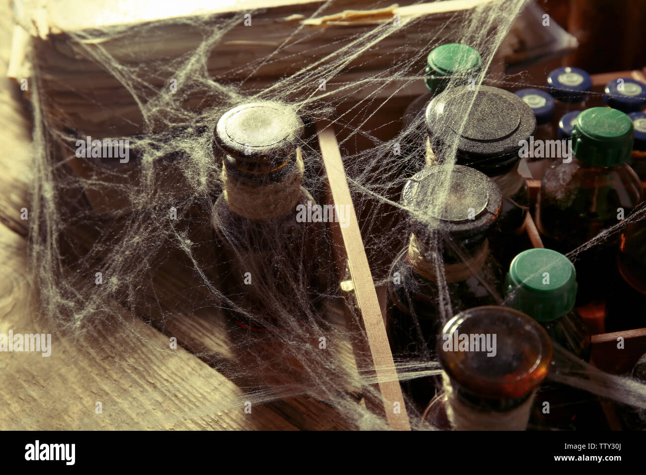 Vintage glass bottles with spiderweb, closeup - Stock Image